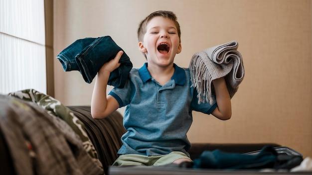 Średni strzał dzieciak trzymający ubrania