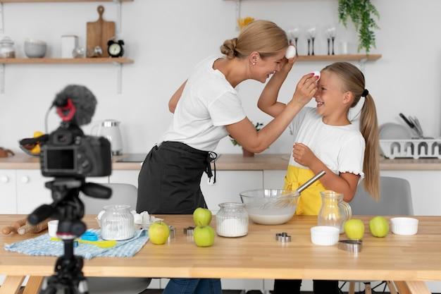 Średni strzał dziecko i kobieta trzymająca jajka