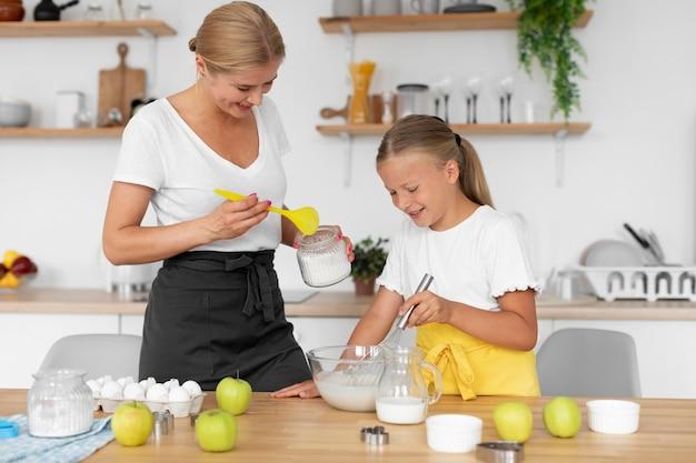 Średni strzał dziewczyna i kobieta robiąca jedzenie
