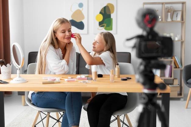 Średni strzał dziewczyna i kobieta siedząca
