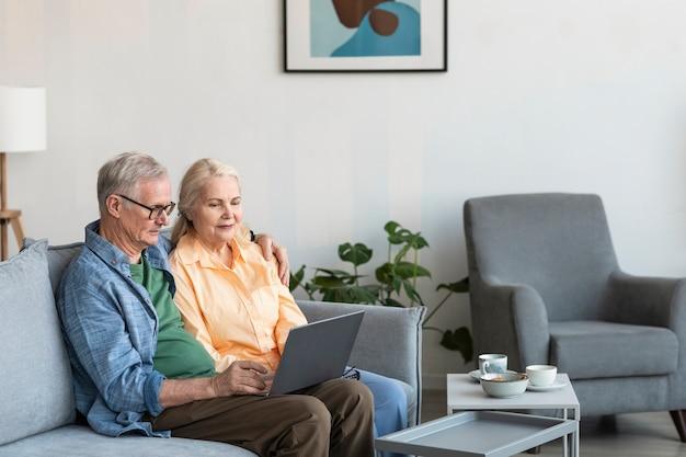 Średni strzał emerytów para z laptopem