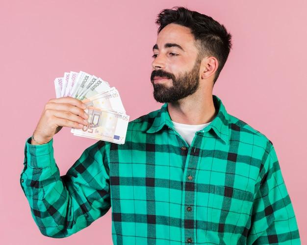 Średni strzał facet trzyma pieniądze