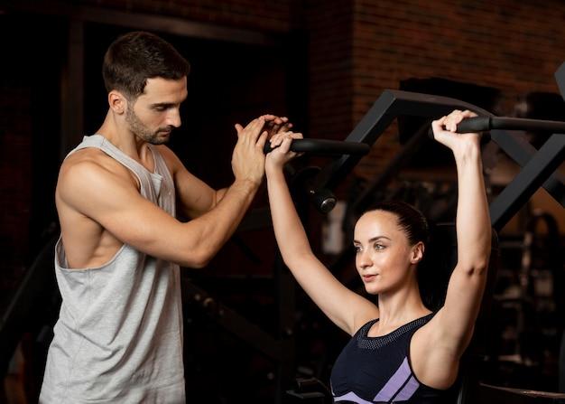 Średni strzał fit kobieta treningu na siłowni