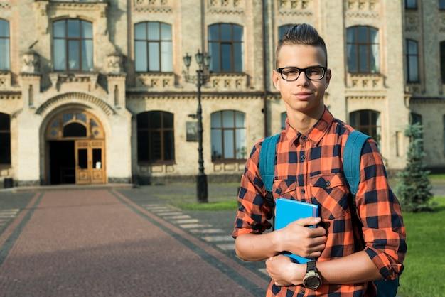 Średni strzał highschool chłopiec trzyma książkę w rękach