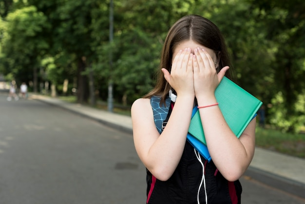 Średni strzał highschool dziewczyna zakrywa jej twarz z rękami