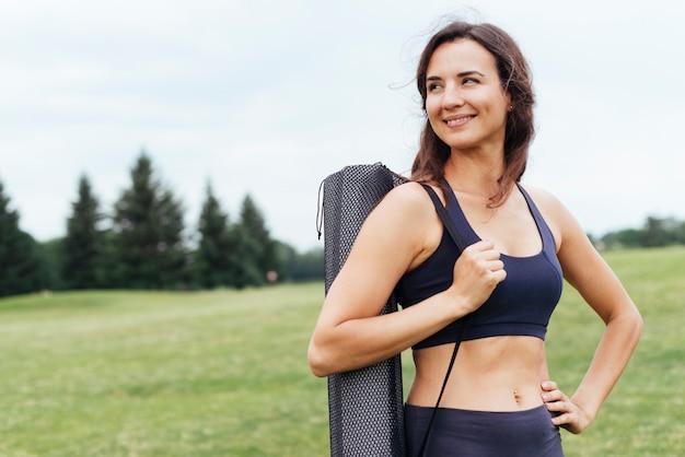 Średni strzał joga kobieta pozuje outdoors
