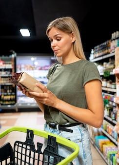 Średni strzał kobieta czytająca etykietę