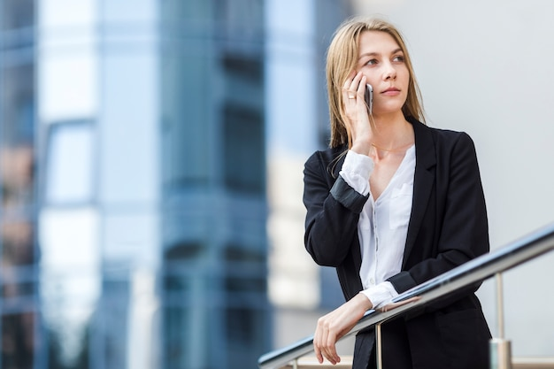 Średni strzał kobieta patrzeje daleko od przed bulding