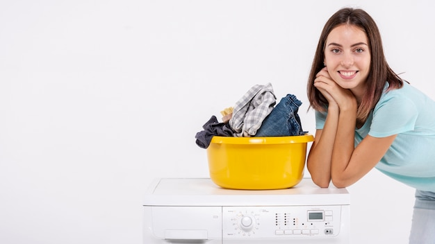 Średni strzał kobieta pozuje blisko pralnianego kosza
