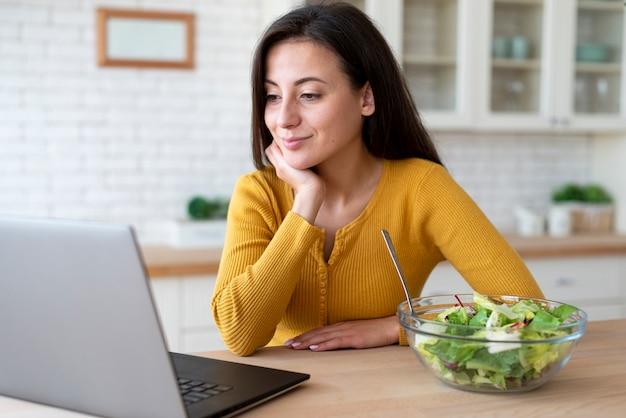 Średni strzał kobieta sprawdza laptop