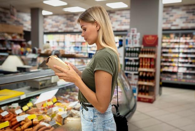 Średni strzał kobieta trzymająca produkty