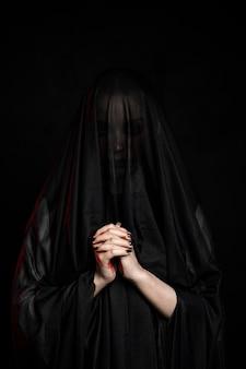 Średni strzał kobieta ubrana w czarny welon