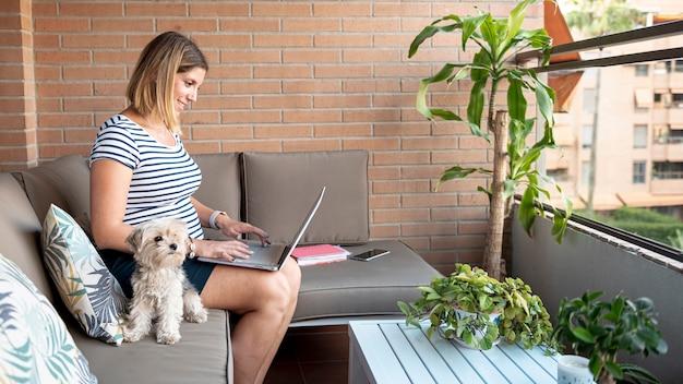 Średni strzał kobieta w ciąży z laptopem i zwierzęciem domowym