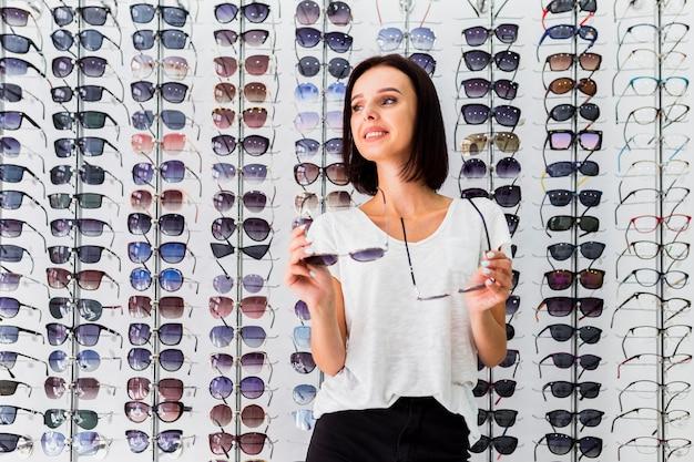 Średni strzał kobiety mienia okularów przeciwsłonecznych pary