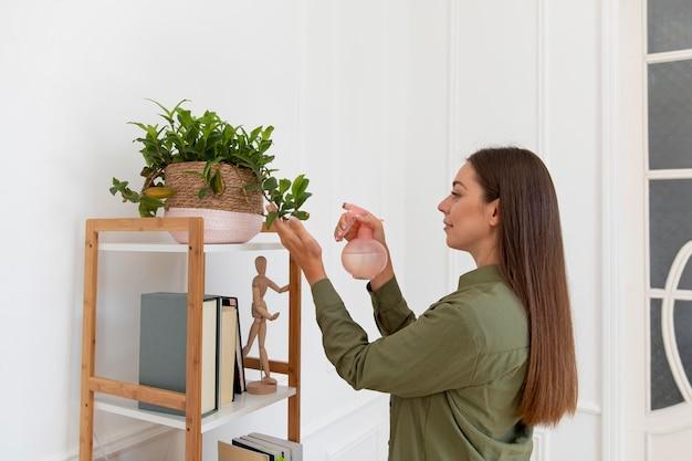 Średni strzał kobiety podlewania roślin