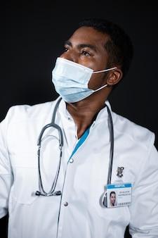 Średni strzał lekarz noszący maskę