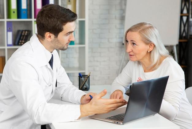 Średni strzał lekarza i pacjenta podczas rozmowy