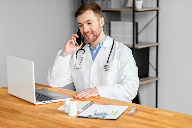 Średni strzał lekarza rozmawiającego przez telefon
