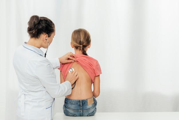 Średni strzał lekarza sprawdzającego dziecko