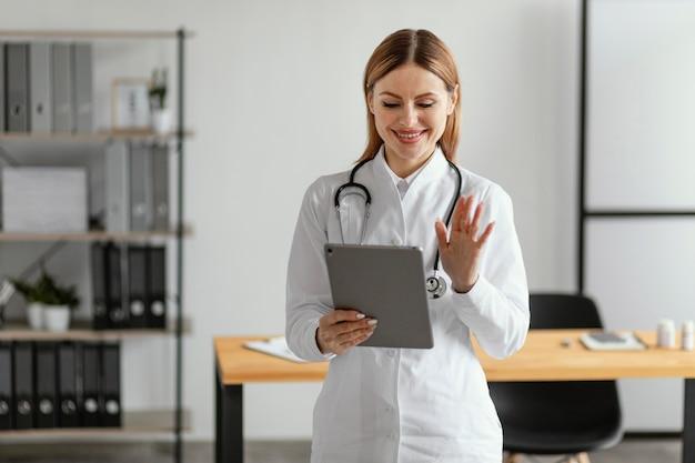 Średni strzał lekarza trzymając tabletkę