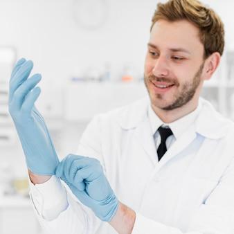 Średni strzał lekarza zakładającego rękawiczki