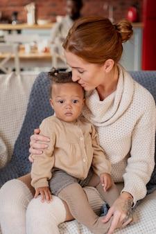 Średni strzał matka całująca dziecko w głowę