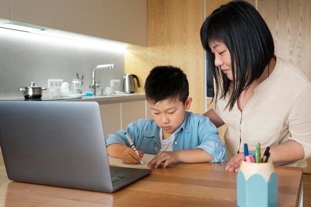 Średni strzał matka i dziecko odrabiają pracę domową