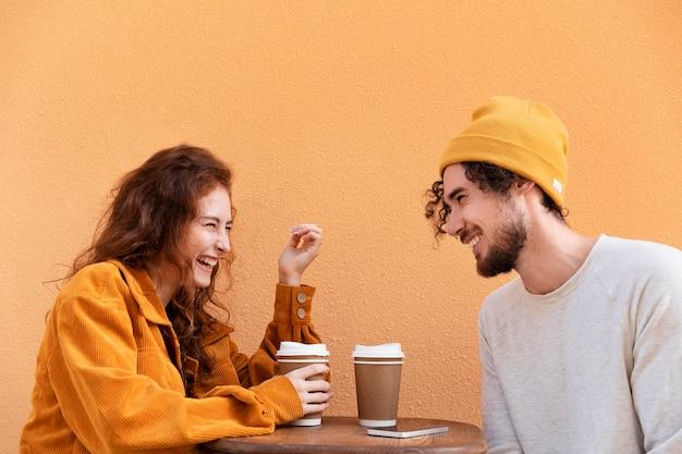 Średni strzał mężczyzna i kobieta z kawą