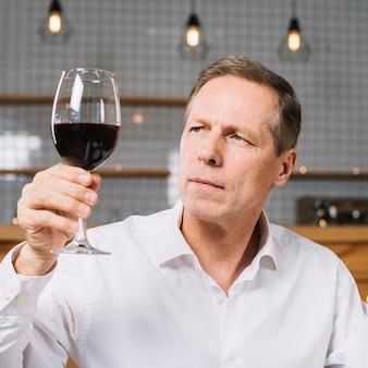 Średni strzał mężczyzna patrzeje szkło wina