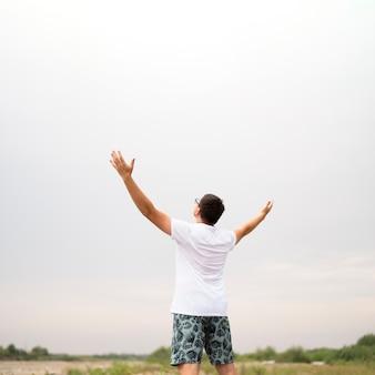 Średni strzał młody człowiek patrzeje niebo