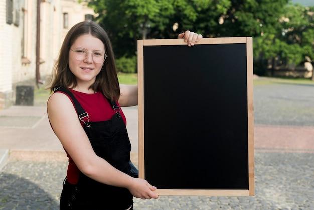 Średni strzał nastoletniej dziewczyny mienia blackboard w rękach