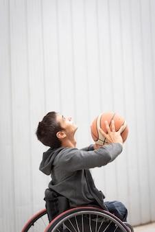 Średni strzał niepełnosprawny mężczyzna grający w koszykówkę
