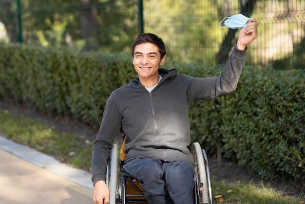 Średni strzał niepełnosprawny mężczyzna trzymający maskę