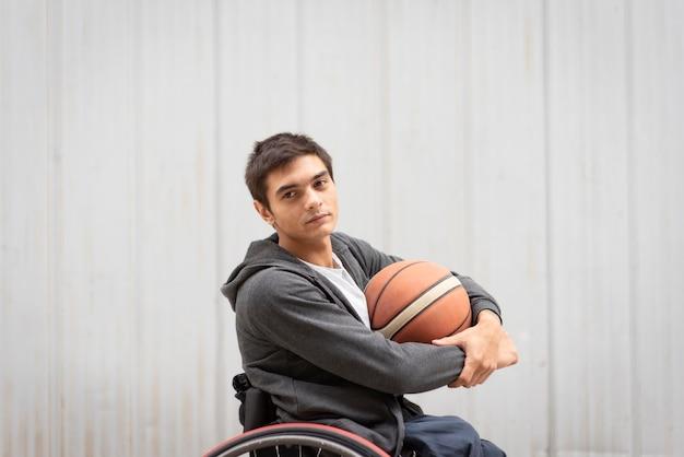 Średni strzał niepełnosprawny mężczyzna trzymający piłkę