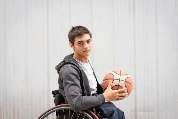 Średni strzał niepełnosprawny mężczyzna z koszykówką