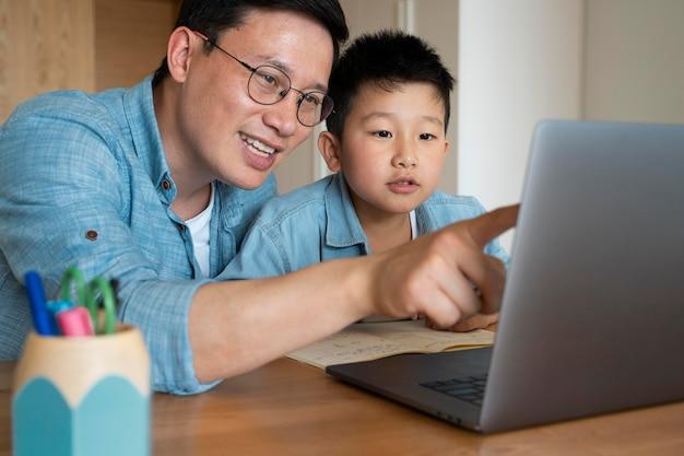 Średni strzał ojciec i dziecko z laptopem