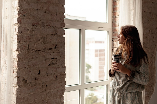 Średni strzał piękna dziewczyna patrząc przez okno