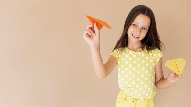 Średni strzał piękna dziewczyna pozuje z papierowymi samolotami