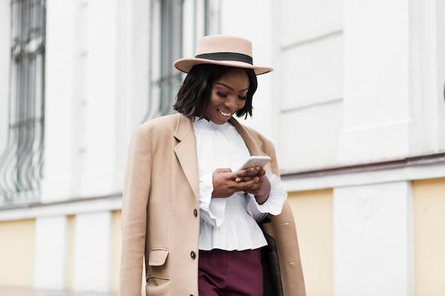 Średni strzał piękna kobieta, patrząc na jej telefon