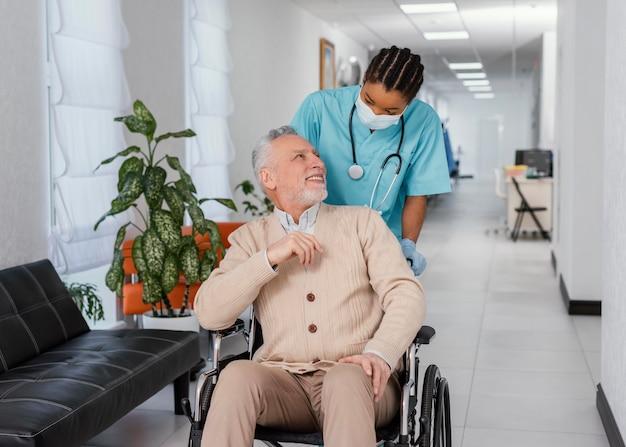 Średni strzał pracownika służby zdrowia pomagającego pacjentowi