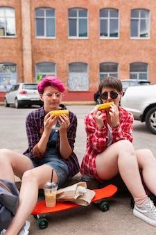 Średni strzał przyjaciele jedzący kukurydzę