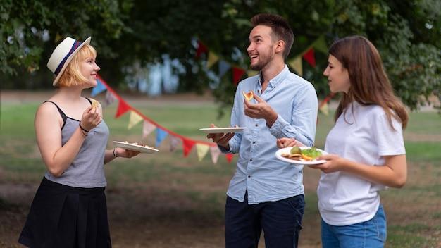 Średni strzał przyjaciele trzymający talerze z jedzeniem