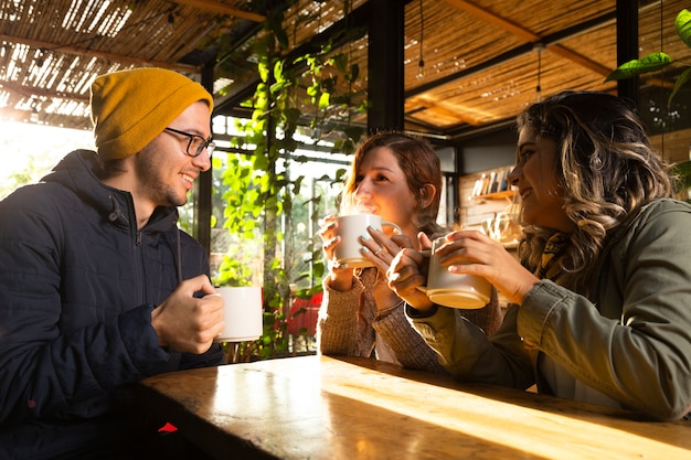 Średni strzał przyjaciół na tarasie kawowym