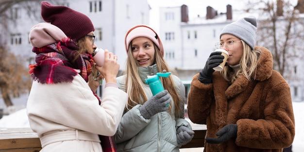 Średni strzał przyjaciół pijących kawę