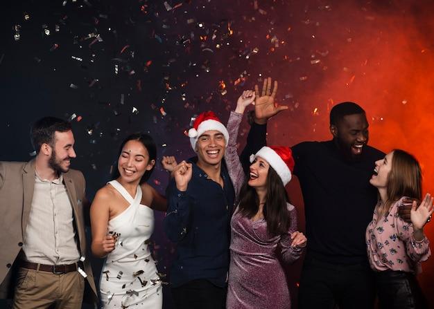 Średni strzał przyjaciół pozowanie na imprezie nowego roku