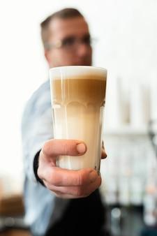 Średni strzał rozmyty barista z kawą