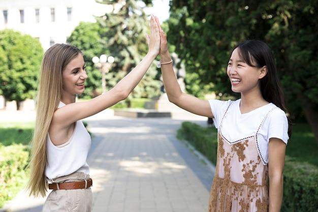 Średni strzał różnorodnych przyjaciół wysokiej fiving