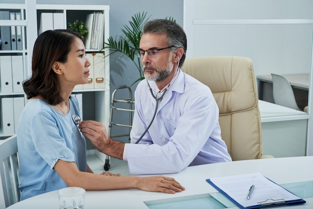 Średni strzał samiec doktorski egzamininuje żeńskiego pacjenta z stetoskopem