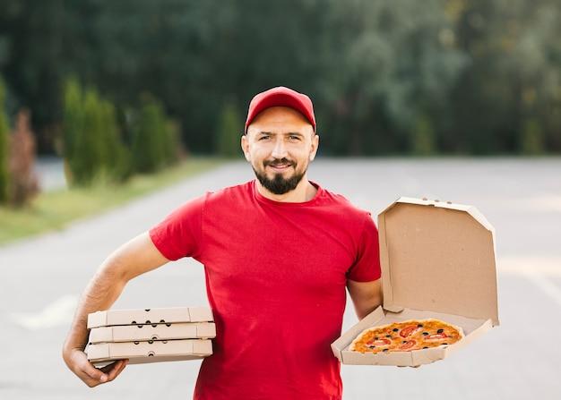 Średni strzał smiley dostawy człowiek z pizzą