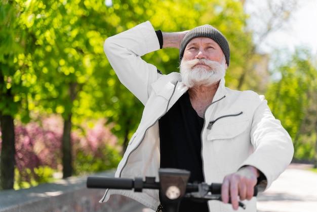 Średni strzał staruszka na skuterze